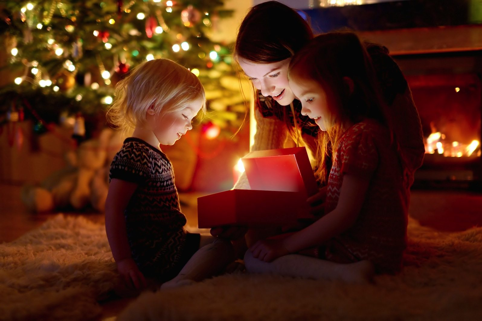 Mother and her daughters opening a Christmas gift