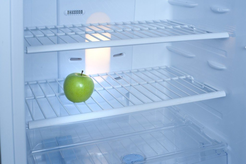 One green apple inside a fridge