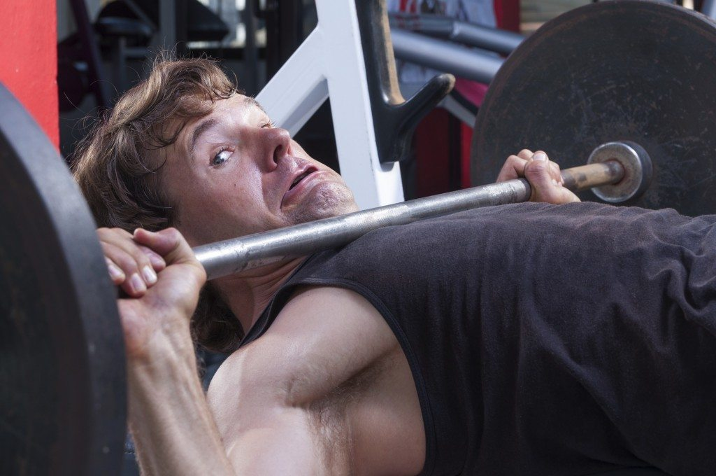 Caucasian man working out in gym is stuck under heavy barbell on bench press