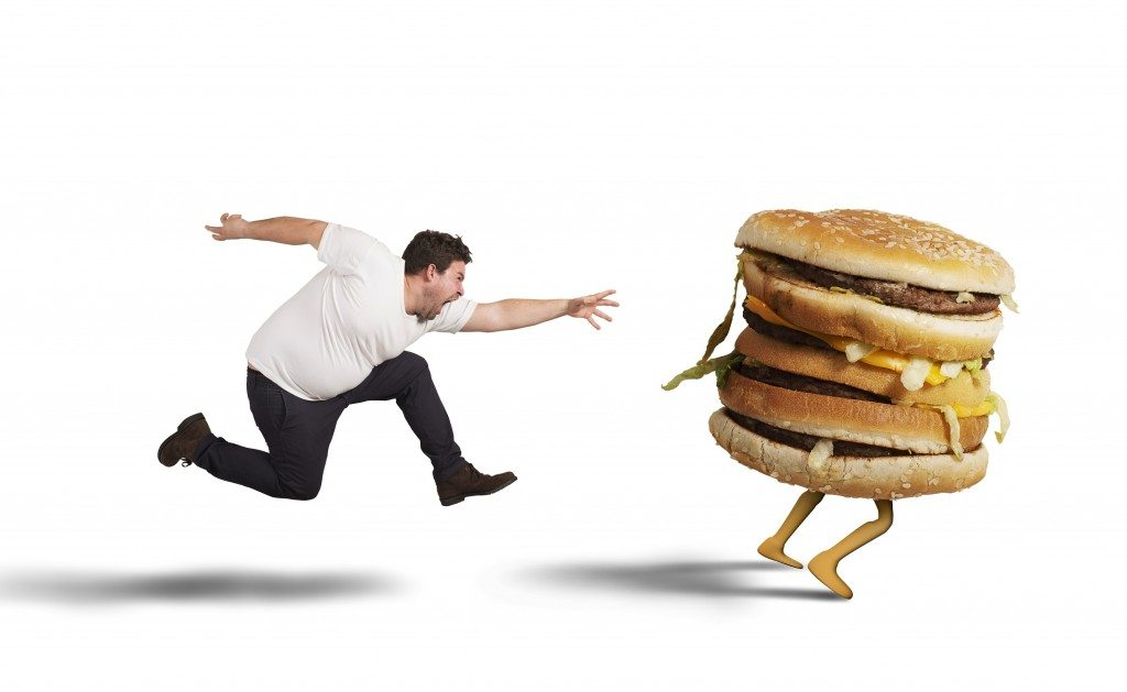 Insatiable fat man runs for catch sandwich
