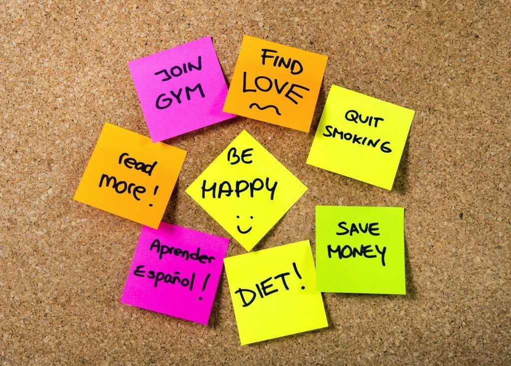Group of New year Resolutions Post it Notes on pink, yellow, orange and green on cork board written with message of diet, join gym, find love, quit smoking and be happy
