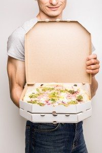 Pizza delivery courier. Young caucasian man holds open box with pizza carbonara